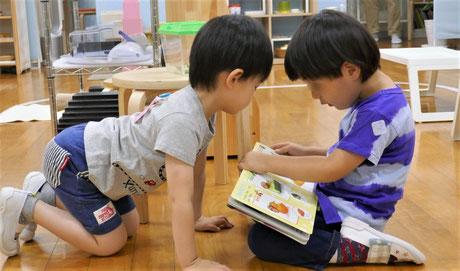 2歳児がモンテッソーリの個別活動でカタツムリを観察したりカタツムリの絵本を見ています。