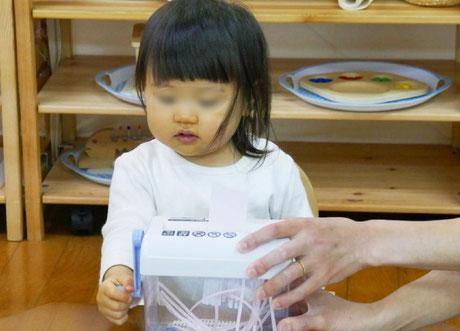 1才児がモンテッソーリの個別活動でシュレッダーの活動をしています。