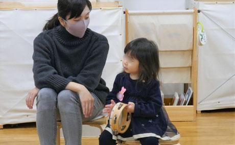 2歳児がリトミックでタンバリンの活動をおこなっているところをお母さまが見守っています。