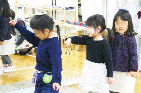 幼稚園児がモンテッソーリの活動で、物を頭の上にのせたり鈴を持って線上歩行をしています。