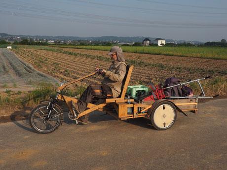 Ein Mann fährt auf einem Massivholz Lastendreirad die Ladefläche ist voll bepackt
