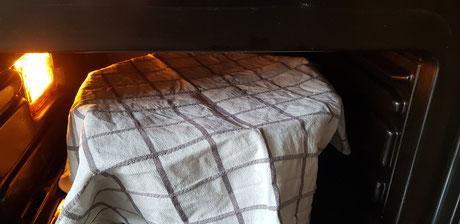 Die Schüssel mit dem Teig mit einem Geschirrtuch abdecken und ca. 50 Minuten an einem warmen Ort stellen und den Teig gehen lassen.
