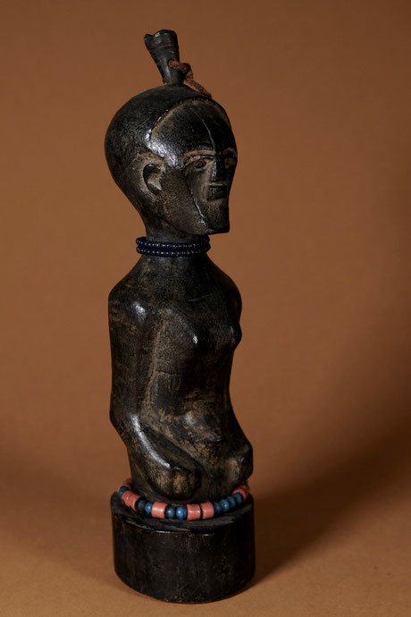 Small Songye Figure with glass beads around neck and waist.