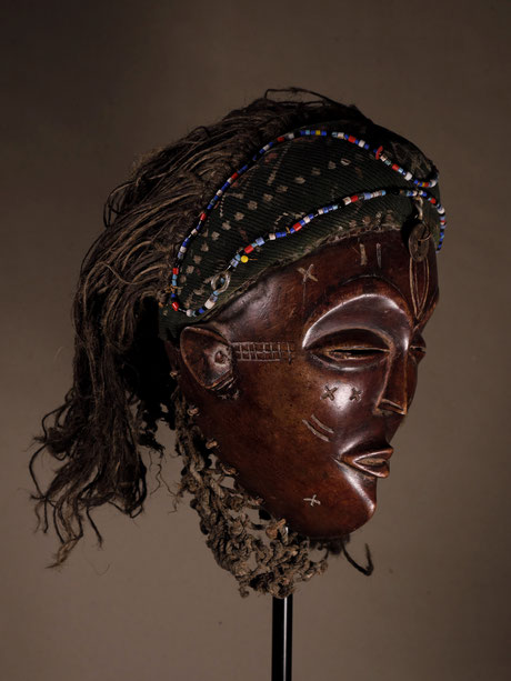 Lueana Mask with reddish wood and matt shining patina. Very beautifully carved and richly decorated.