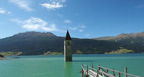 Der Turm im Reschensee in der Ferienregion Reschenpass im Vinschgau in Graun und Reschen am See. Blick Richtung Elferspitze bei herrlichem Bergwetter im Sommer.