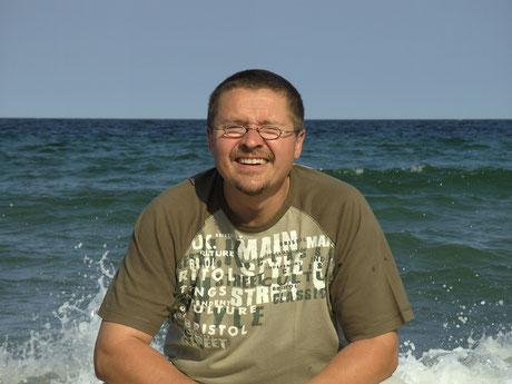 Mann am Strand der Ostsee hockend mit Wellen im Hintergrund
