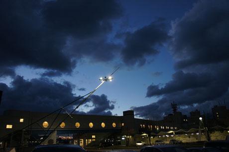 夕方5時の直江津駅。鉛色の空から漏れる青空と丸窓の明かり。乗客たちがホッとして駅に降り立ちます