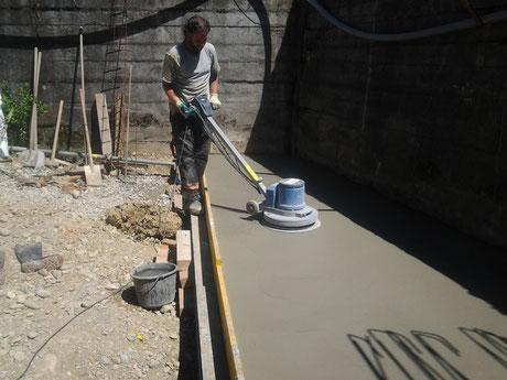 Fabian beim Abglätten von einem Betonboden.