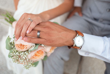 woman and man with wedding rings holding hands
