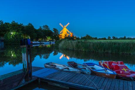 Blaue Stunde in Greetsiel mit den beleuchteten Zwillingsmühlen  und Tretbooten im Vordergrund