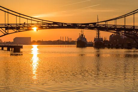 Sonnenuntergang Kaiser-Wilhelm-Brücke in Wilhelmshaven mit Blick auf das Feuerschiff Weser und den Tonnenleger Kapitän Meyer und das Atlantic Hotel