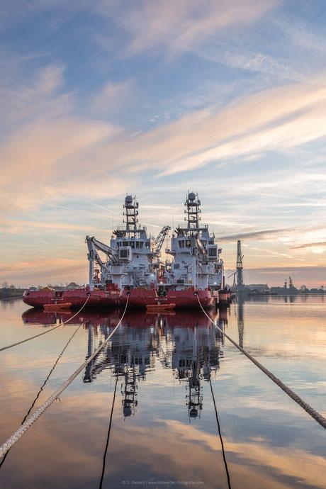 Vertäute Arbeitsboote im Sonnenuntergang.