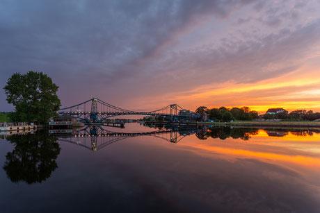 Sonnenuntergang mit einem dramatischen Himmel an der Kaiser-Wilhelm-Brücke in Wilhelmshaven