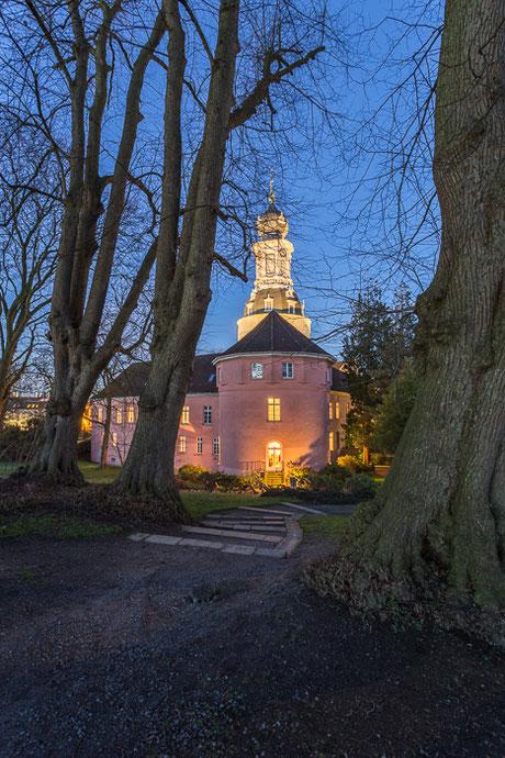 Rückseite Schloss Jever in Friesland zur Blauen Stunde mit Bäumen im Vordergrund