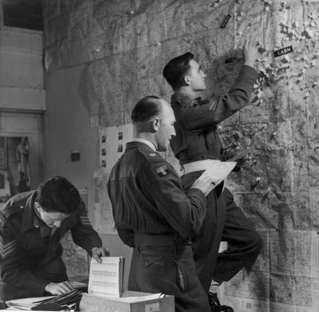 Major Pedder and two others inspect a map, which shows the locations of individual graves or small groups of buried soldiers.