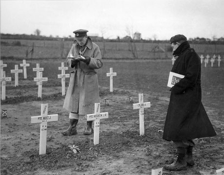 The 48th Graves Concentration Unit commanded by Major Pedder: Two officers look for a grave among the rows of crosses.