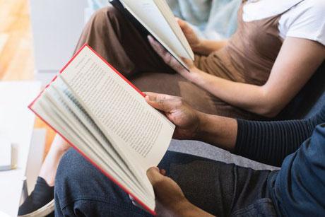 Deux personnes assises cote à cote en train de lire.