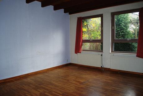 Wohnzimmer mit Heizkörpern und einer kalten Außenmauer.