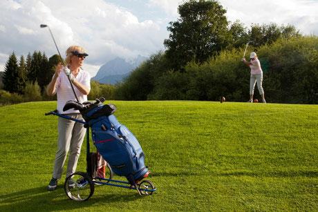 Golffoto mit zwei Damen, eine holt gerade zum Schlag aus