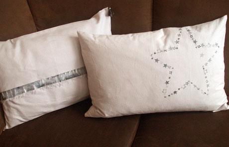 weiße Kissen auf braunem Sofa, eines mit sichtbarer Webkante, das andere mit Sternendruck