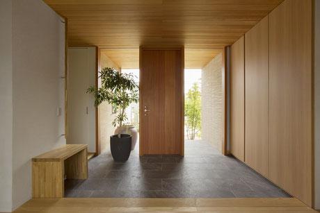 建物に合わせて大きなガラス張りの玄関、天井材を内と外を合わせる事で繋がりを感じます。写真右側は全て靴収納ですが取っ手と付けず、扉に手掛け加工をすることでスッキリ綺麗に見えます。玄関