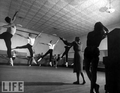 Ballet Mistress Margaret Craske conducting class for leaping dancers John Kriza, Michael Maule & Peter Gladke (L-R) as Nora Kaye leans against piano (R).