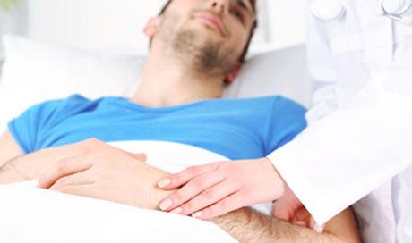 Mann liegt im Krankenhausbett und genießt bestmögliche ärztliche Betreuung durch die private Krankenversicherung