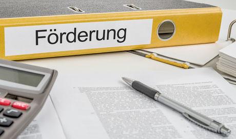 Ordner, Taschenrechner, Kugelschreiber und Förderbedingungen um Förderdarlehen beantragen zu können