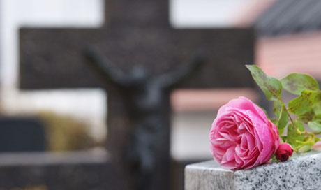Ein Grabstein als Jesuskreuz, davor eine rosa Rose gibt Angehörigen Hoffnung, weil sie finanziell durch eine Risikolebensversicherung abgesichert sind