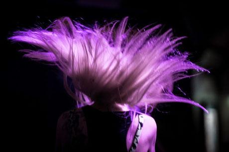 Mila auf der Bühne mit werfenden Haaren im lila Scheinwerferlicht