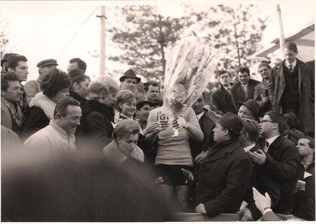 M.Vigna su di un podio improvvisato riceve i fiori tra la folla. Foto TLS