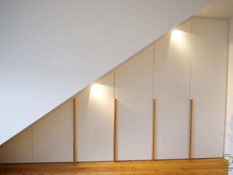 Weißer Kleiderschrank millimetergenau an Dachschräge angepasst, Drempel Schrank in weiß mit Massivholz Eichen-Griffleisten, Dachschrägenschrank Schräge links mit weißen Fronten u. Massivholz-Eichengriffleisten