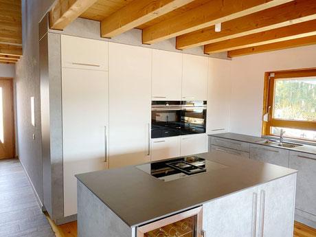 Kücheninsel mit Muldenlüfter, Küche mit integrierter Speisekammer, Schranktür im Hochschrank, Kücheninsel mit Hochschrankzeile u. integrierter Speisekammertür, Küche in Betonoptik, offene Inselküche mit versteckter Speisekammertür, Kochinsel