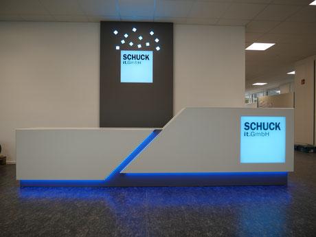 Verkausfstheke in weiß mit indirekter LED-farbwechslender RGB-Beleuchtung, weiße Empfangstheke in L-Form mit beleuchteter Logo-Gestaltung mit einem Lightpanel