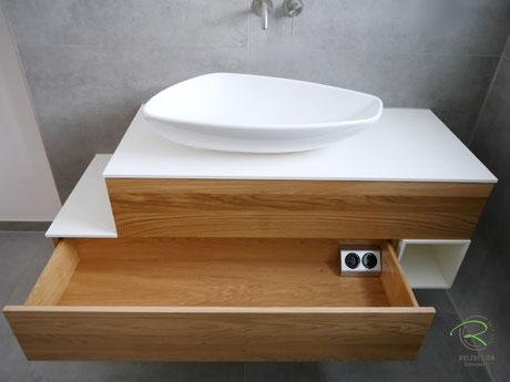 Badschrank mit breiten Schubladen mit integrierter Doppelsteckdose, Waschbeckenunterschrank Eiche Massivholz u. weißer Auflageplatte u. offenem Handtuchfach hängend, wandhängender Waschtischunterschrank in Massviholz-Eiche u. weißer Auflageplatte