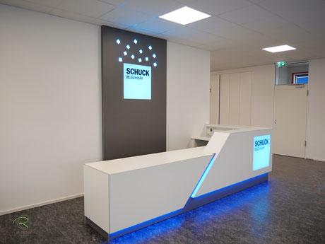 Verkaufstresen in weiß mit blauer, indirekter LED Beleuchtung, Verkausfstheke in weiß mit indirekter LED-farbwechslender RGB-Beleuchtung, weiße Empfangstheke in L-Form mit beleuchteter Logo-Gestaltung mit einem Lightpanel
