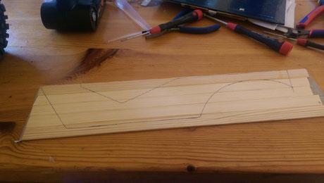 (1) Holzleisten auf dem Faserband nebeneinander anordnen und anschließend die Leisten untereinander mit Superkleber verkleben. Wenn der Kleber getrocknet ist kann man mit den Original Karosserieteilen die Konturen auf des Holz übertragen.