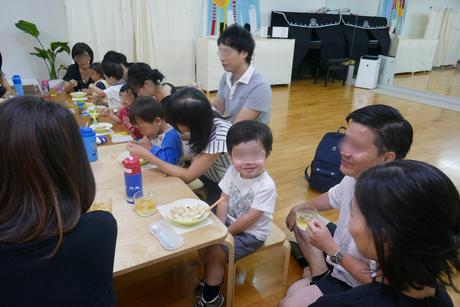 0歳児、1歳児の生徒が、お母様やお父様といっしょにつくった月見団子を美味しそうに食べています。