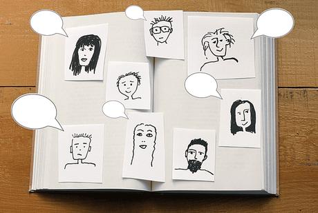 Aufgeklapptes Buch mit gezeichneten Gesichtern zur optischen Darstellung von Facebook