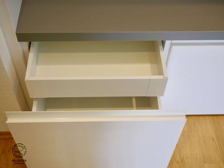 Schubladen im Garderobenschrank mit integrierter Griffleiste, Garderobenschrank mit Schuhschrank u. Massivholz-Eichen-Griff in weiß Hochglanz u. offener Garderobennische mit Kleiderstange in staubgrau mit indirekter Beleuchtung