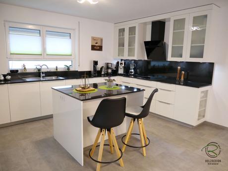 Kleine Kücheninsel mit 2 Sitzplätzen, weiße, offene Hochglanz Wohnküche mit Granit Arbeitsplatte Nero Assoluto poliert mit kleiner Kochinsel u. Sitzplatz, raumhoher Hochschrankzeile mit Glasvitrinen als Küchenabschluss u. Verbindung zum Wohnraum