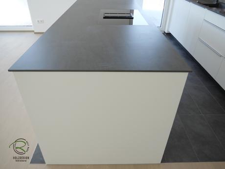 Kücheninsel in weiß mit Keramik-Neolith Arbeitsplatte mit Highboard für Kühl-Gefirrschrank u. Backofen mit brauner, indirekt beleuchteter Nischenrückwand u. Aluminium Griffleiste auf der Front u. flächenbündiger Induktion-Muldenlüfter
