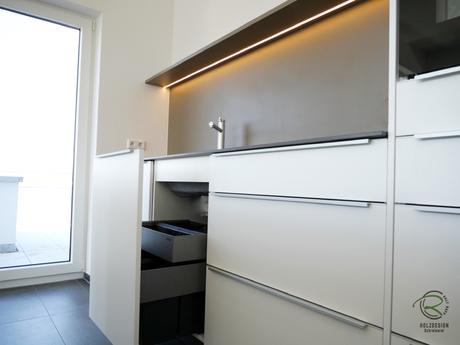 Kücheninsel weiß mit Mülltrennsystem Select 60/3 mit Orga-Schublade Aufbewahrung von Spülbürste o. Schwämme, weiße Kücheninsel mit Aluminium Griffleiste auf Front,  Schreinerküche weiß mit Keramik-Neolith Arbeitsplatte u. beleuchteter Nischenrückwand