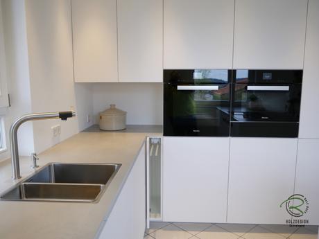 Anstatt Eckpassleisten ein Handtuchhalter Auszug für grifflose, weiße Design Küche mit oriongrauen Schubladen von Blum Legrabox mit Halbkochinsel 12 mm Keramik Arbeitsplatte