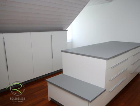 Ankleiderzimmer in Dachschräge mit Kommode u. Einbauschränken in weiß u. grau, Einbauschränke in Ankleide nach Maß angepasst an die Dachschräge mit Sitzmöglichkeit u. Schmutzwäsche-Schublade