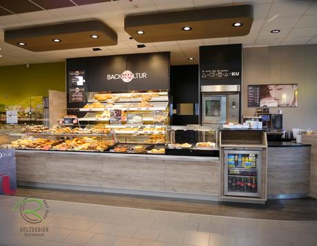 Pendeltür mit Glas, Individuelle Einrichtung für den Ladenbau in Holzdekor, Bäckereieinrichtung K&U Backkultur in Aldingen, Ladenbau für Bäckerrei, Einrichtung für Bäckerei mit Kaffee in hellen Holzdekor, indivduelle Ladeneinrichtung für Bäckerei,