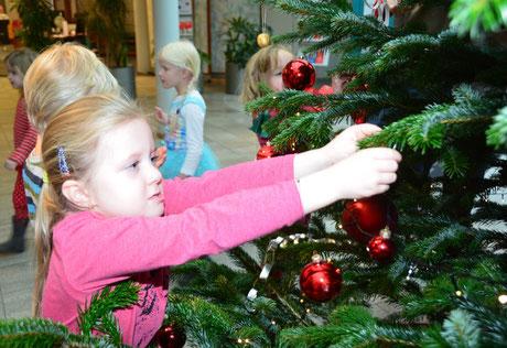 Konzentriert schmückt die kleine Romy den Weihnachtsbaum.