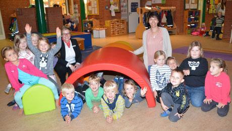 Filialleiterin Jana Panten (li) und Kita-Leiterin Astrid Beste (re) freuen sich mit den Kindern über die neuen Spielgeräte.