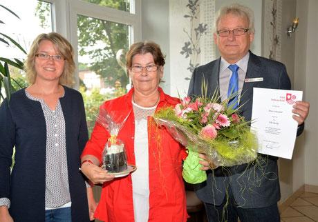 Tanja Knaack (li) und Dirk Michels (re) gratulieren der Jubilarin Elke Radtke.