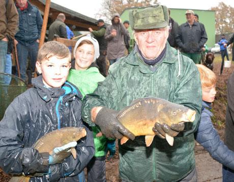 Dominik (12)  aus Schenefeld und Wolfgang Gülck aus Oldendorf präsentieren die Mühlenteichkarpfen.